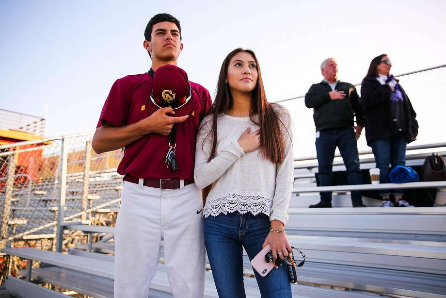 Couple Ryan Miller and Kelly Danoff pause for the national anthem ahead of a senior lacrosse game at Cardinal Newman in Santa Rosa. Photo: Gabrielle Lurie / The Chronicle