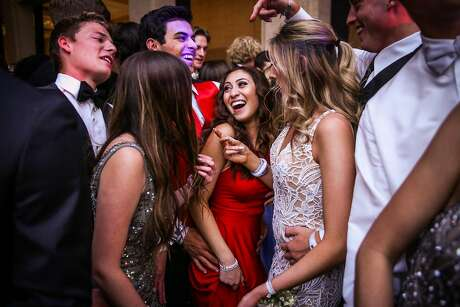Kelly Danoff (center), her boyfriend Ryan Miller (third from left) and their other friends dance during prom night at the Bentley Reserve in San Francisco, California, on Sunday, April 29, 2018. Both Ryan and Kelly lost their homes in the Santa Rosa fires last October. Their school was also severely damaged.