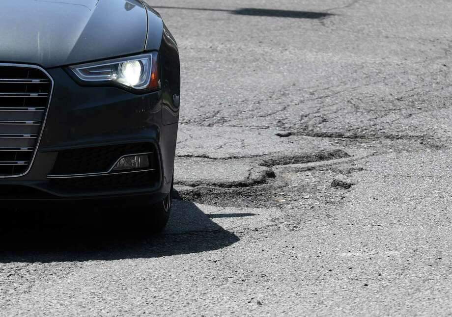 A car is driven across potholes on South Swan St. near the South Mall Arterial on Wednesday, May 2, 2018, in Albany, N.Y. (Will Waldron/Times Union) Photo: Will Waldron, Albany Times Union