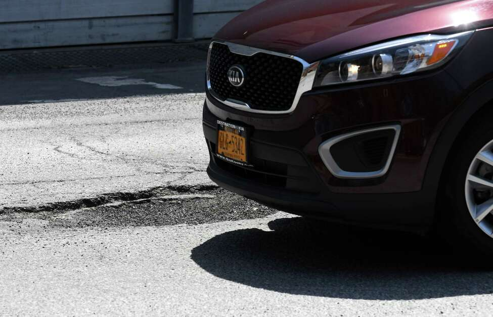 A car is driven across potholes on South Swan St. near the South Mall Arterial on Wednesday, May 2, 2018, in Albany, N.Y. (Will Waldron/Times Union)