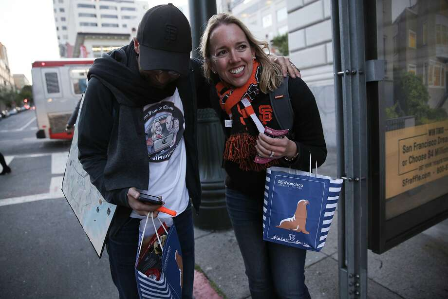 Peter Hartlaub and Heather Knight hug after running and making it to the 3-Jackson bus at Van Ness Avenue and Sutter Street. Photo: Santiago Mejia / The Chronicle