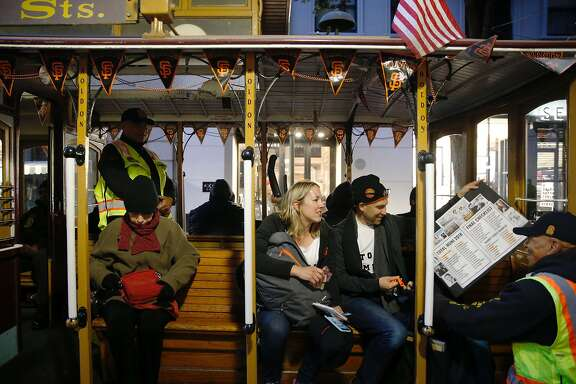 San Francisco Chronicle reporter Peter Hartlaub and Heather Knight ask an SFMTA employee to cross off the a San Francisco Giants decorates Powell Street Cable Car from their list around 6 a.m. during the Total Muni 2018 challenge, an attempt to ride every Muni line in one day in San Francisco, Calif. Monday, April 30th, 2018.