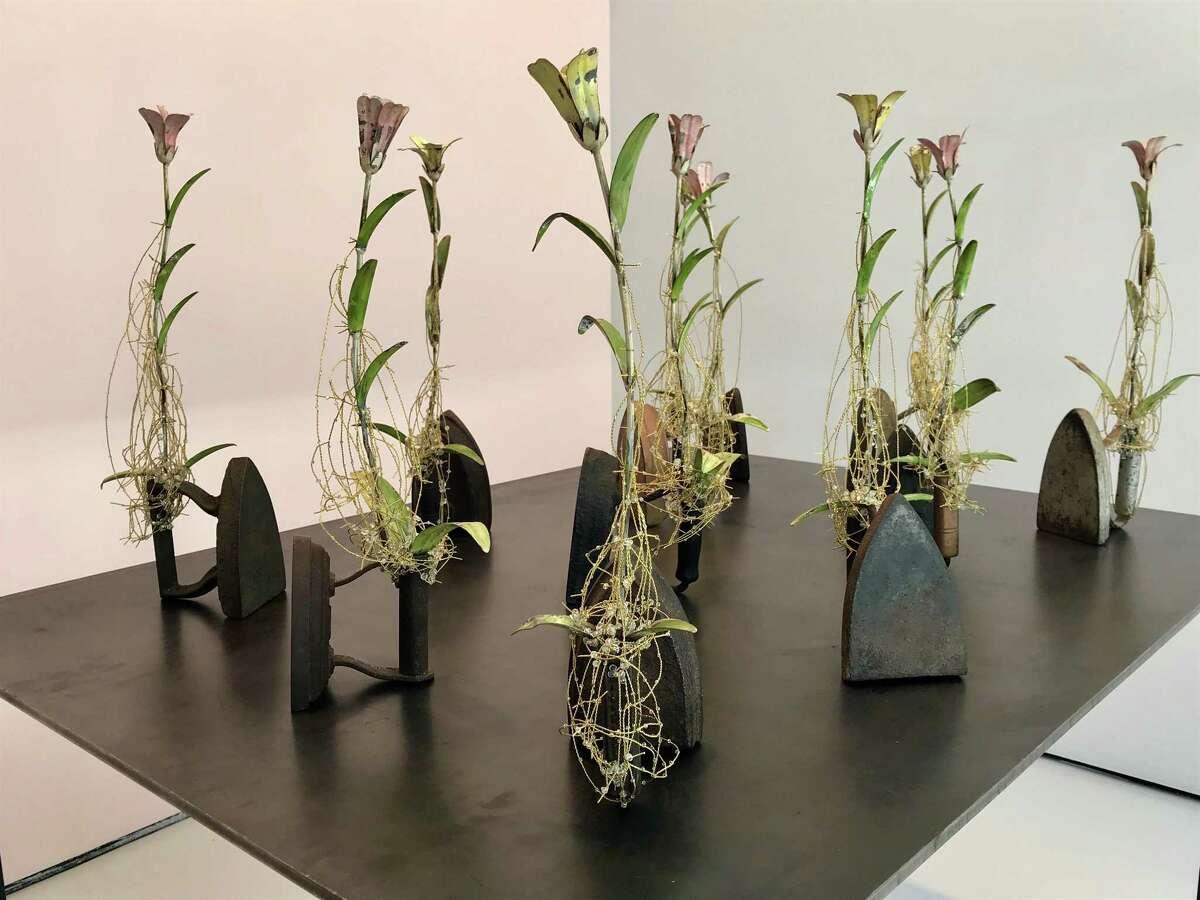"""""""Second Wives,"""" consisting of 11 antique irons and wired metal flowers with crystals on a steel table, is among the works in Karin Broker's show """"Love Me, Love Me Not"""" at McClain Gallery."""