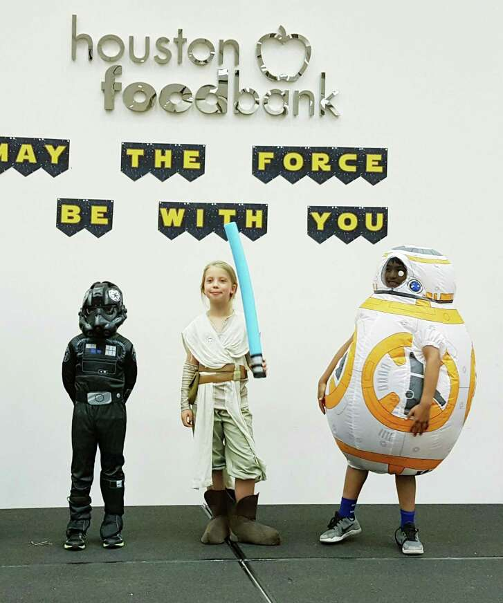 "Kids pose as ""Star Wars"" characters during the Houston Food Bank's May the 4th event."
