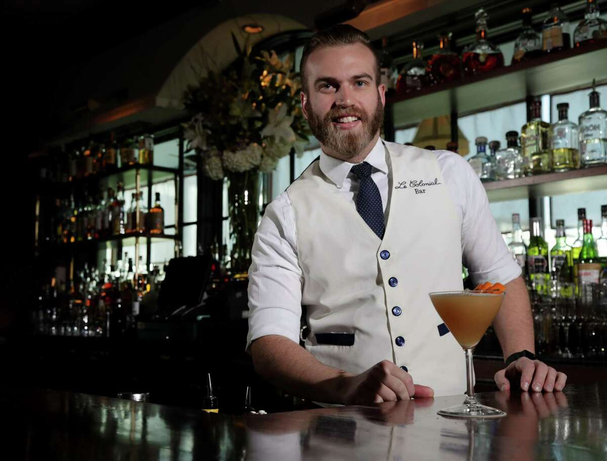 Alex Zuelke, a bartender at Le Colonial, poses for a portrait with a tamarind sour at the restaurant, Thursday, April 26, 2018, in Houston. ( Jon Shapley / Houston Chronicle )