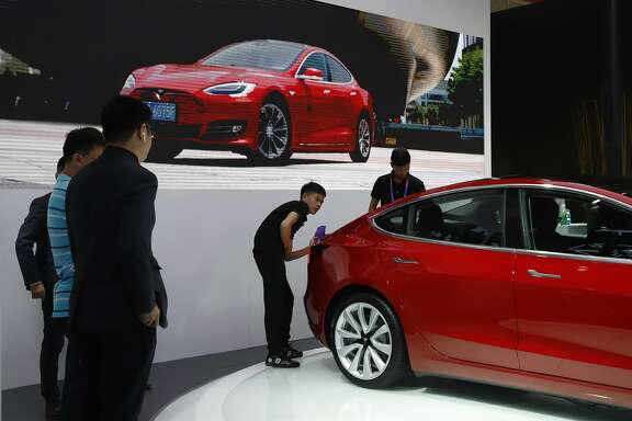 A worker cleans a sedan from Tesla during Auto China 2018 in Beijing, China, Thursday, April 26, 2018. Auto China 2018, the industry's biggest sales event this year, is overshadowed by mounting trade tensions between Beijing and U.S. President Donald Trump, who has threatened to hike tariffs on Chinese goods including automobiles in a dispute over technology policy. (AP Photo/Ng Han Guan)