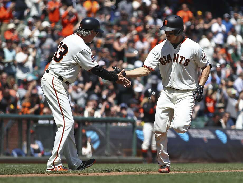 Nick Hundley is congratulated by third base coach Ron Wotus after hitting a two-run home run off San Diego's Clayton Richard in the fourth inning of Wednesday's game. Photo: Ben Margot / Associated Press