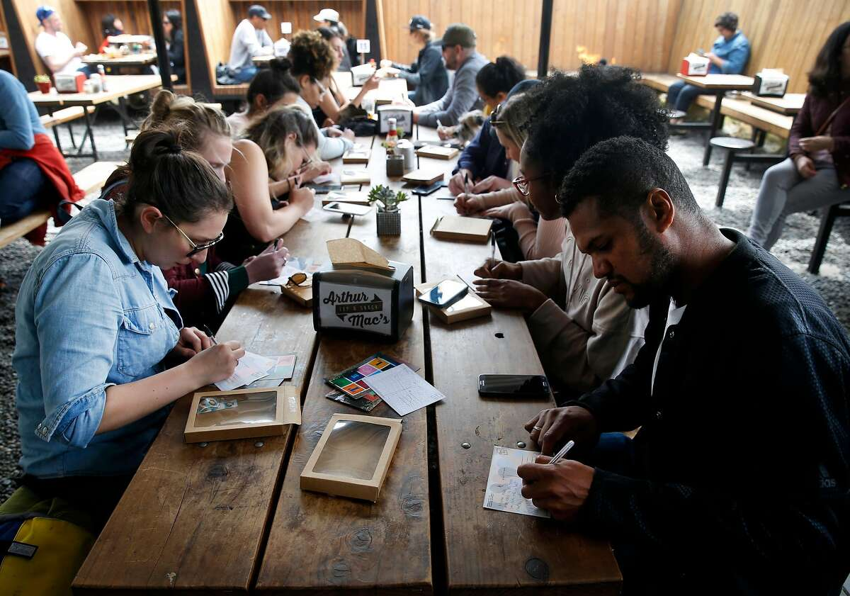 Stephanie Hooper (left) and Thomas Jones (right) write in postcards at Arthur Mac�s beer garden on Jena Pruitt�s walking postcard scavenger hunt tour in the Temescal neighborhood in Oakland, Calif. on Saturday, April 28, 2018. Pruitt's postcard tour is one of the most popular events available through the Airbnb Experience portal.
