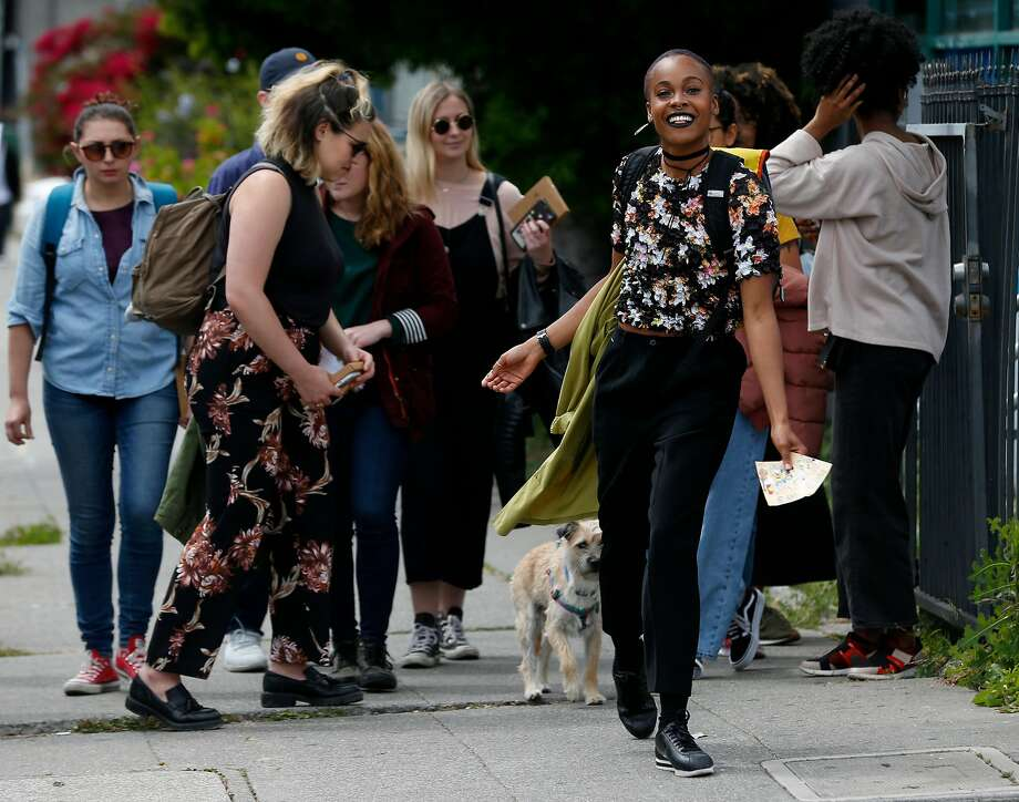 Jena Pruitt leads a walking postcard scavenger hunt tour in the Temescal neighborhood in Oakland, Calif. on Saturday, April 28, 2018. Pruitt's postcard tour is one of the most popular events available through the Airbnb Experience portal. Photo: Paul Chinn / The Chronicle