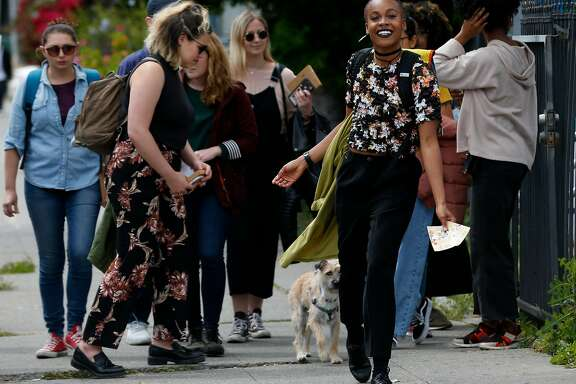 Jena Pruitt leads a walking postcard scavenger hunt tour in the Temescal neighborhood in Oakland, Calif. on Saturday, April 28, 2018. Pruitt's postcard tour is one of the most popular events available through the Airbnb Experience portal.