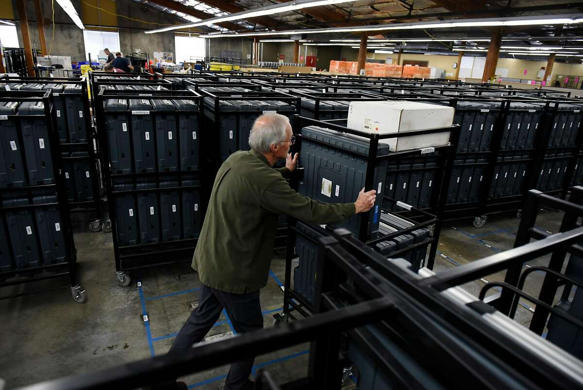 Election technician Bill Gibson wheels a rack of tested and sealed Hart Intercivic eSlate voting machines in a warehouse at the San Mateo County Registration & Elections Division building in San Mateo, CA, on Wednesday May 2, 2018.