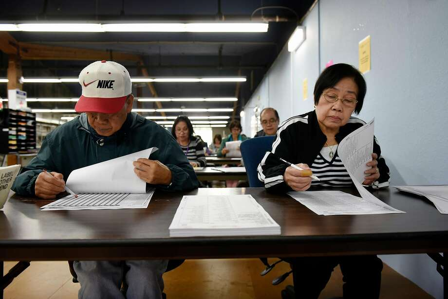 Santi and Cristina Rimando of Daly City manually mark paper ballots for testing at the San Mateo County Registration & Elections Division building. Photo: Michael Short / Special To The Chronicle