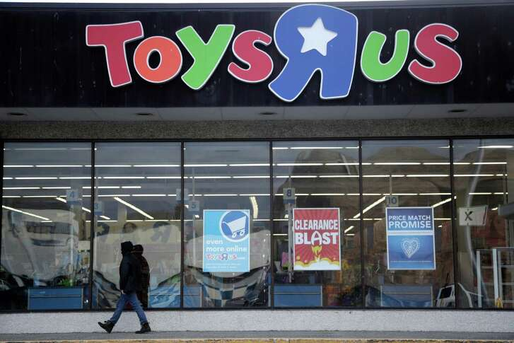 """FILE- This Jan. 24, 2018, file photo shows a person walking near the entrance to a Toys R Us store, in Wayne, N.J.  Canada's Fairfax Financial Holding has placed a bid of $300 million to buy Toys R Us's Canadian operations in bankruptcy. According to court papers filed late Thursday, April 19, 2018, the bidder is taking on a role of a """"stalking horse"""" in a court-approved auction set for Monday in New York. That means it could be outbid in the auction if other buyers come in with a higher offer. The bid from Fairfax surpassed the $215 million offer that Isaac Larian, the CEO of privately held toy company MGA Entertainment, made last week. (AP Photo/Julio Cortez, File)"""