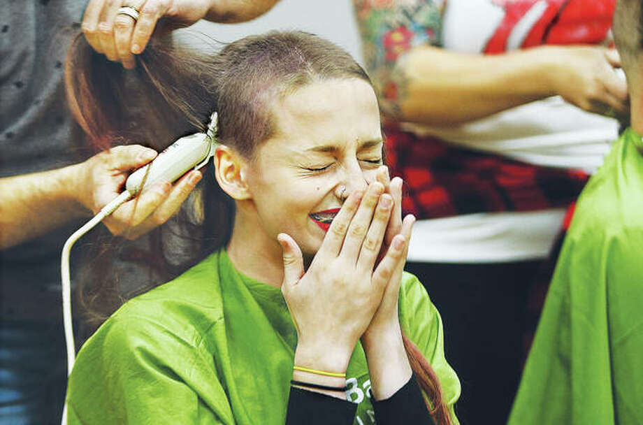Civic Memorial High School student Amaya Stief reacts as her hair is cut off in the school gym Wednesday as part of a fundraiser by the National Honor Society at the school, which raised more than $8,000. Several people, mostly students, had their heads shaved to raise money for the child cancer research organization. Photo:       John Badman | The Telegraph