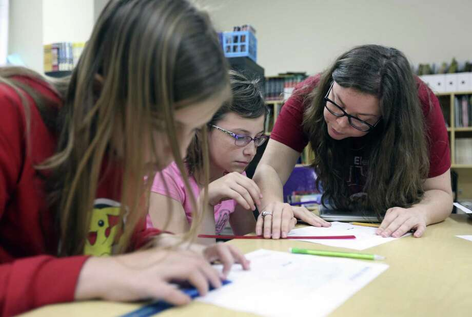 Teacher Meredith Jacobsen, right, helps students Reese Comeaux, left, and Eva Pratt to determine Wednesday, May 2, 2018 how far the Canary Islands are from San Antonio. Photo: William Luther, Staff / San Antonio Express-News / © 2018 San Antonio Express-News