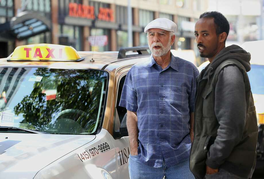 Taxi drivers, including Jack Gruber (left) who has been driving a cab for 25 years, and Kiros Ghebremedhin wait for passengers at the Marquis Marriott hotel in San Francisco. Photo: Liz Hafalia / The Chronicle
