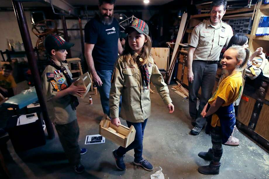 "FILE - In this March 1, 2018, file photo, Tatum Weir, center, carries a tool box she built as her twin brother Ian, left, follows after a Cub Scout meeting in Madbury, N.H. Fifteen communities in New Hampshire are part of an ""early adopter"" program to allow girls to become Cub Scouts and eventually Boy Scouts. For 108 years, the Boy Scouts of America's flagship program for older boys has been known simply as the Boy Scouts. With girls soon entering the ranks, the BSA says that iconic name will change to ""Scouts BSA."" The change will take effect in February 2019. (AP Photo/Charles Krupa, File) Photo: Charles Krupa, Associated Press"