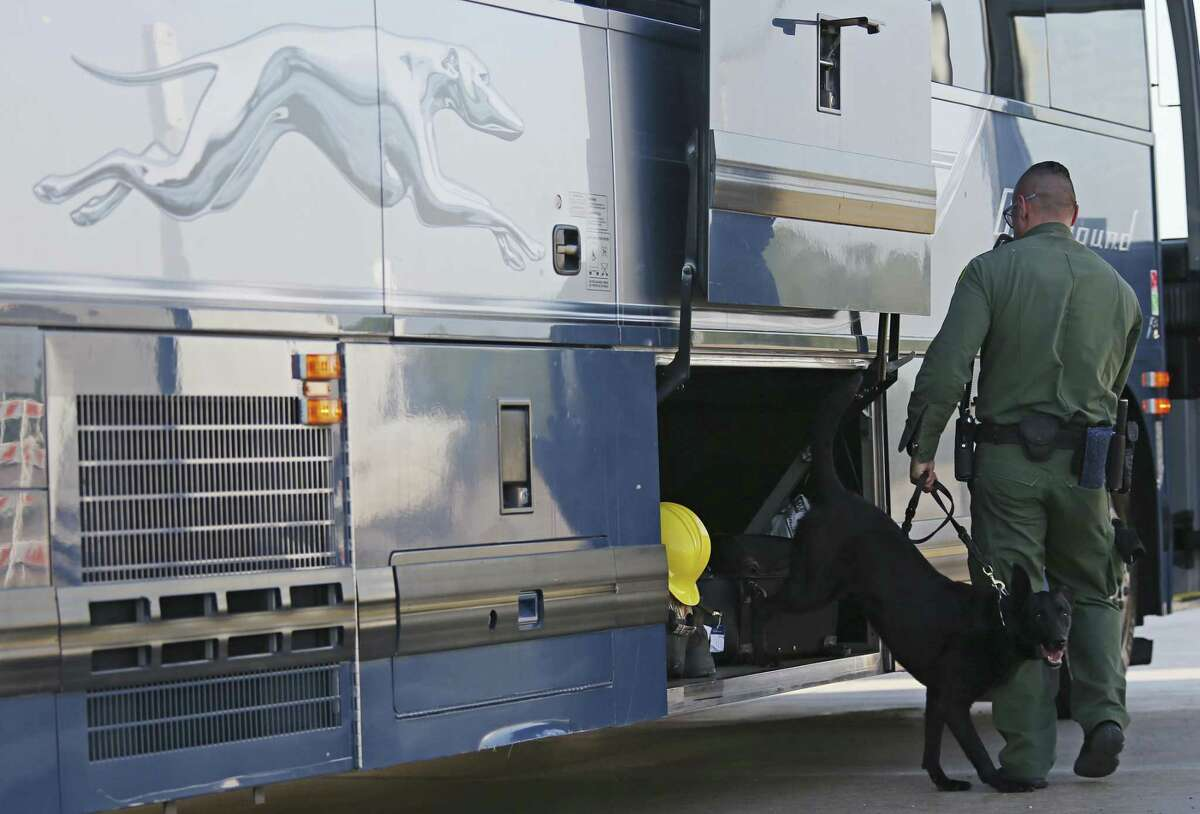 A U.S. Border Patrol K-9 unit works a commercial bus at the Laredo checkpoint located about 29 miles north on IH-35 near Encinal, Texas, Thursday, April 12, 2018.