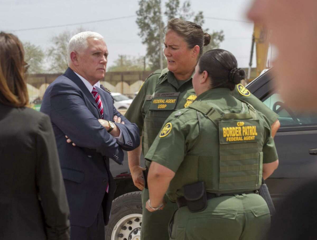 Vice President Mike Pence listens to acting Border Patrol Chief Carla Provost, center, and Gloria Chavez, Chief Patrol Agent for the El Centro Sector, right, at the site where a stretch of fence is being replaced with a much taller designed barrier on April 30, 2018 in Calexico, Calif.