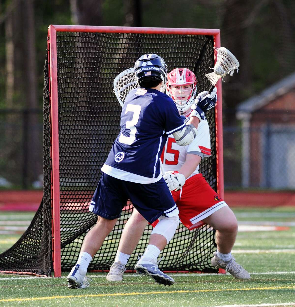 Wilton's Ryan McDermott goes one-on-one against Greenwich goalie Connor Santry on Wednesday.