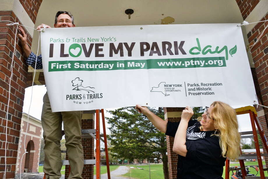 "Mike Greenslade, left, and Jennifer Emmons hang a banner for ""I Love My Park Day"" at Saratoga Spa State Park in 2016. More than 135 events are planned for Saturday, May 5, 2018 at parks statewide. (John Carl D'Annibale / Times Union)"