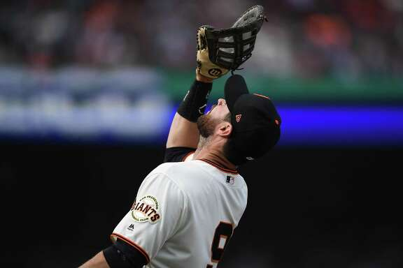Brandon Belt #9 of the San Francisco Giants catches a foul pop-up off the bat of Cody Bellinger #35 of the Los Angeles Dodgers in the top of the six inning of a Major League Baseball game at AT&T Park on April 7, 2018 in San Francisco, California.