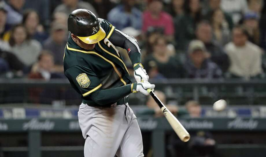Oakland Athletics' Mark Canha connects for a home run against the Seattle Mariners during the ninth inning of a baseball game Wednesday, May 2, 2018, in Seattle. (AP Photo/Elaine Thompson) Photo: Elaine Thompson / Associated Press