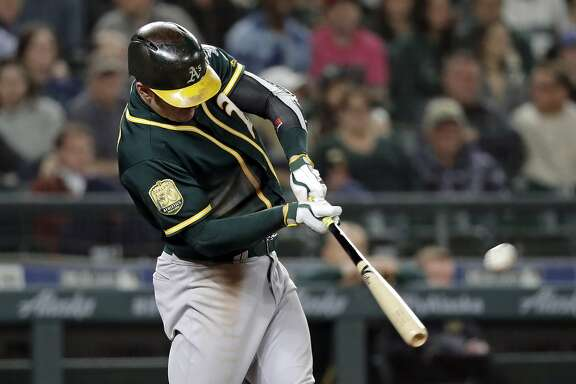 Oakland Athletics' Mark Canha connects for a home run against the Seattle Mariners during the ninth inning of a baseball game Wednesday, May 2, 2018, in Seattle. (AP Photo/Elaine Thompson)