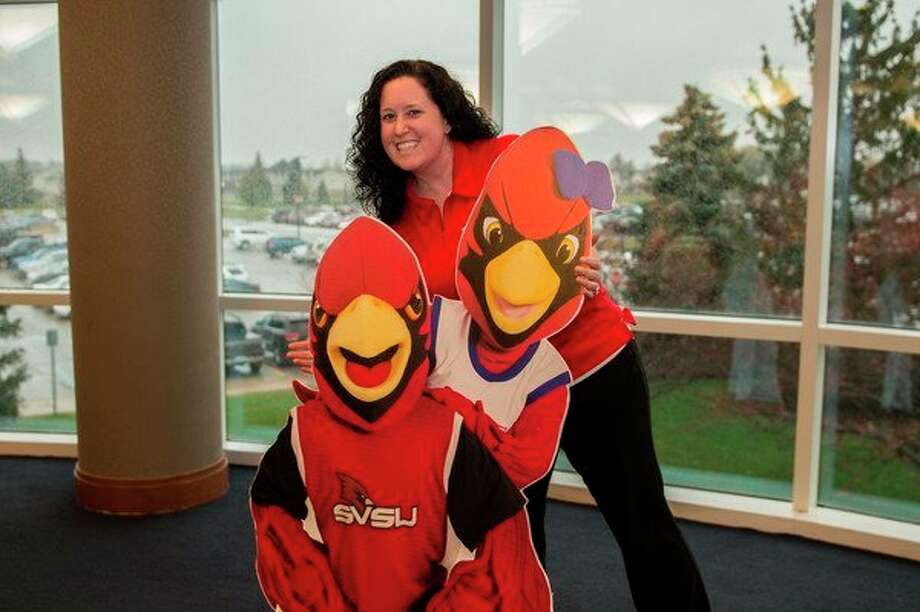 Rachel Florence-Spaetzel, director of orientation programs at Saginaw Valley State University, poses with cutouts of SVSU mascots Coop and Scarlet. (Photo provided)