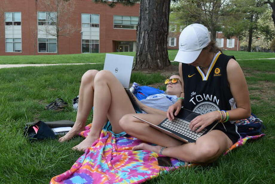 Illinois College sophmores Madi Peyton (front) and Grace Yaunches take advantage of nice weather Tuesday to study outside for their final exams.