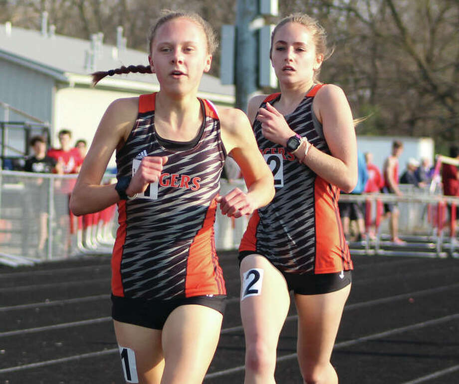 Edwardsville's Abby Schrobilgen (left) and Hannah Stuart run 1-2 in the 3,200 meters during the Madison County Meet on April 24 in Highland. The Tigers' juniors repeated the 1-2 finish Wednesday in the 3,200 at the SWC Meet in Collinsville. Photo:       Greg Shashack / For The Telegraph