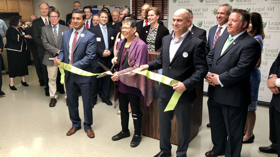From left to right, Sanjeeve DeSoyza, president of the Board of Directors of the Legal Aid Society of Northeastern New York, Lillian Moy, executive director of LASNNY, and Empire State Development cut the ribbon for LASNNY's new Center for Civil Legal Services in Albany's West Hill neighborhood. (Massarah Mikati/Times Union)