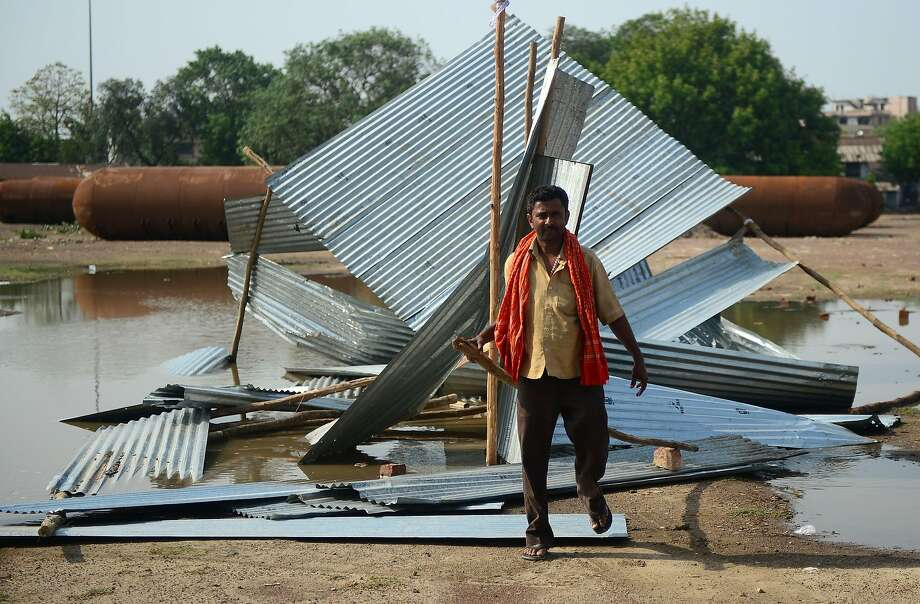 An Indian man passes next to a destroyed tin shed in Allahabad. Damage was caused by flying debris, lightning and rain as wind speeds from the dust storm reached 100 mph in some areas. Photo: Sanjay Kanojia / AFP / Getty Images