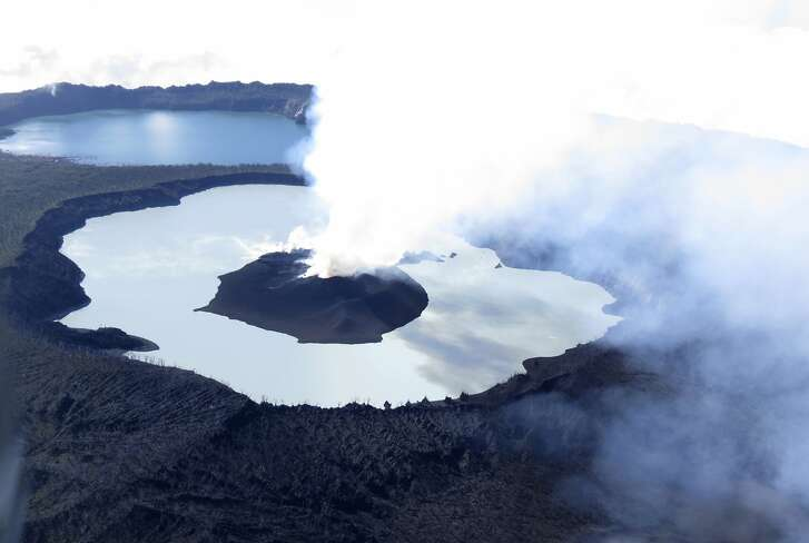 FILE - In this Oct. 1, 2017, file photo provided by GeoHazards Divison, Vanuatu Meteorological and GeoHazards Department, steam rises from the volcanic cone that has formed in Lake Vui near the summit of Ambae Island, Vanuatu. The Pacific nation of Vanuatu is preparing to permanently evacuate the entire population of one of its islands as thick ash spewing from a volcano kills crops, dirties water supplies and fouls the air, government spokesman said Thursday, May 3, 2018. (Brad Scott/GeoHazards Divison, VMGD via AP, File)