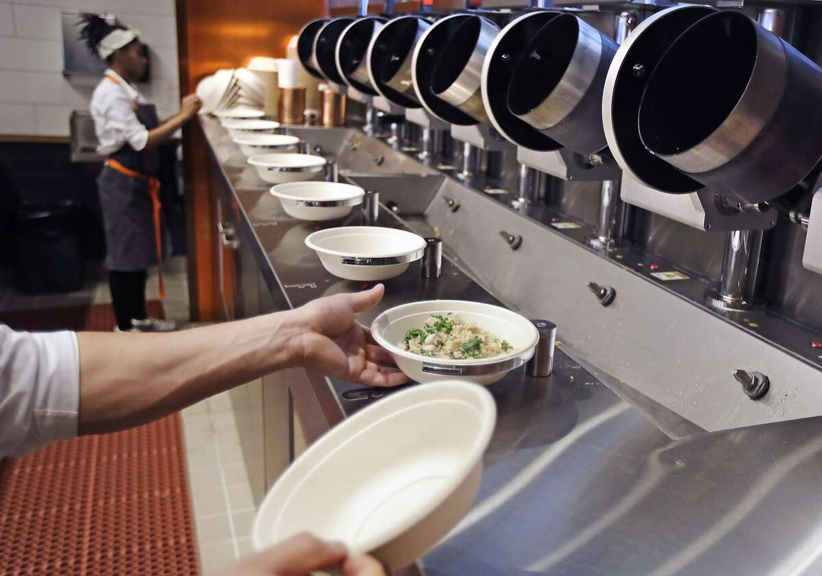 A worker lifts a bowl off the line at Spyce, a restaurant which uses a robotic cooking process.