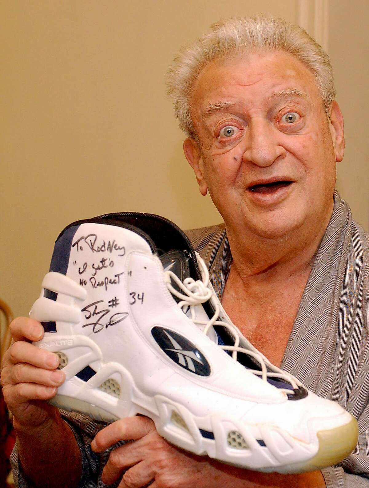 ** FILE ** Comedian Rodney Dangerfield holds up a shoe autographed by Shaquille O'Neal that says