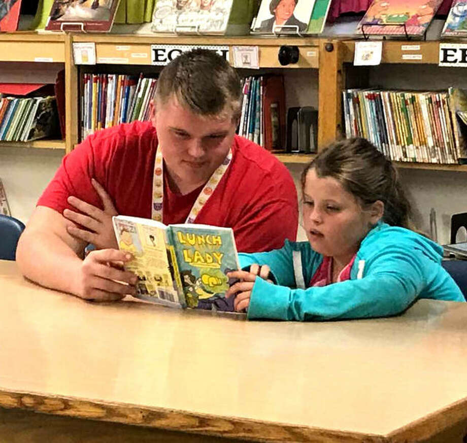 A Spanish 2 student from Alton High School and third-grade student from West Elementary use their time Thursday to read a book together. Photo:       Kelsey Schulz | The Telegraph
