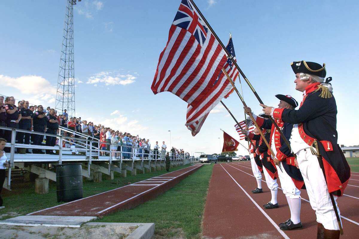 Neighbors Spectators at Unicorn Stadium in New Braunfels stand at attention as flags are presented by the Sons of the American Revolution during the national anthem Tuesday, September 18.