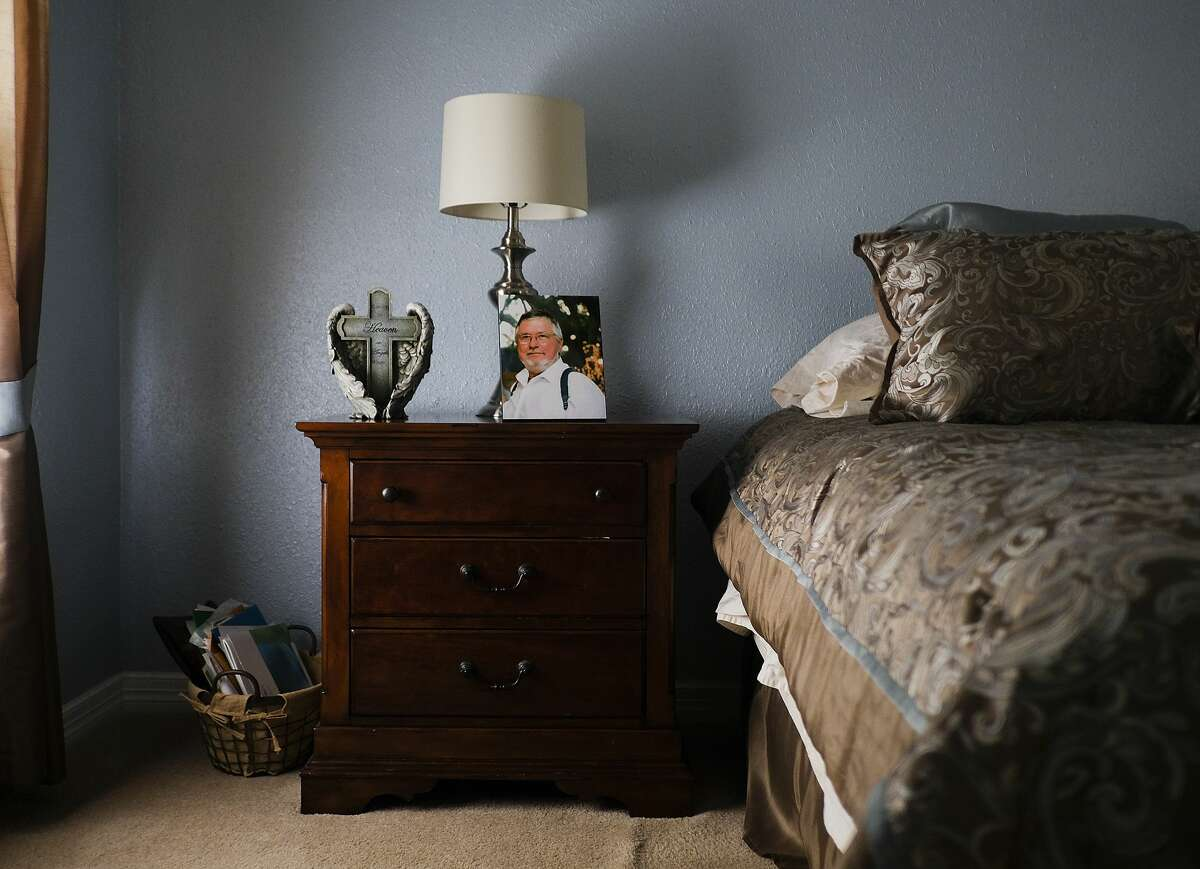 A photo of David Kveton sits on the nightstand next to his widow's bed at their home in Fort Bend County, Texas.