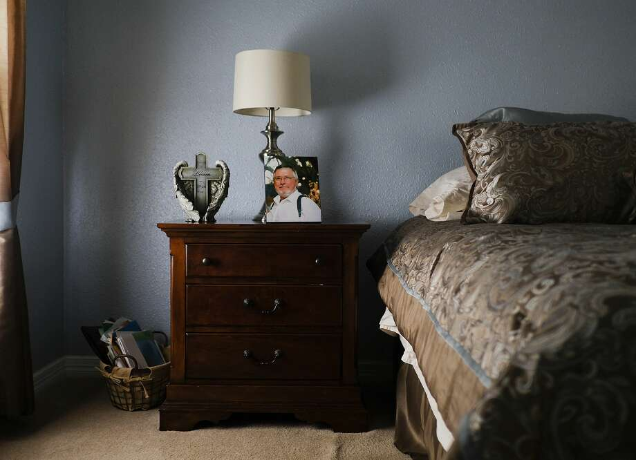 A photo of David Kveton sits on the nightstand next to his widow's bed at their home in Fort Bend County, Texas. Photo: Elizabeth Conley/Houston Chronicle