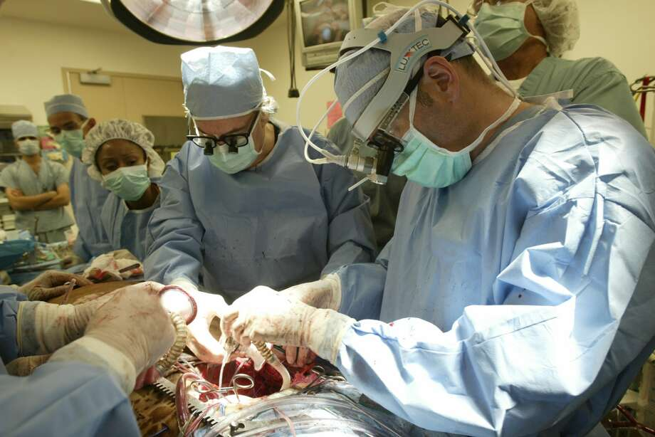 "Dr. O.H. ""Bud"" Frazier, center, and Dr. Billy Cohn, right, replaced a cow's heart with a pair of pumps in the animal lab at St. Luke's Episcopal Hospital and Texas Heart Institute in 2005. Photo: Steve Ueckert"
