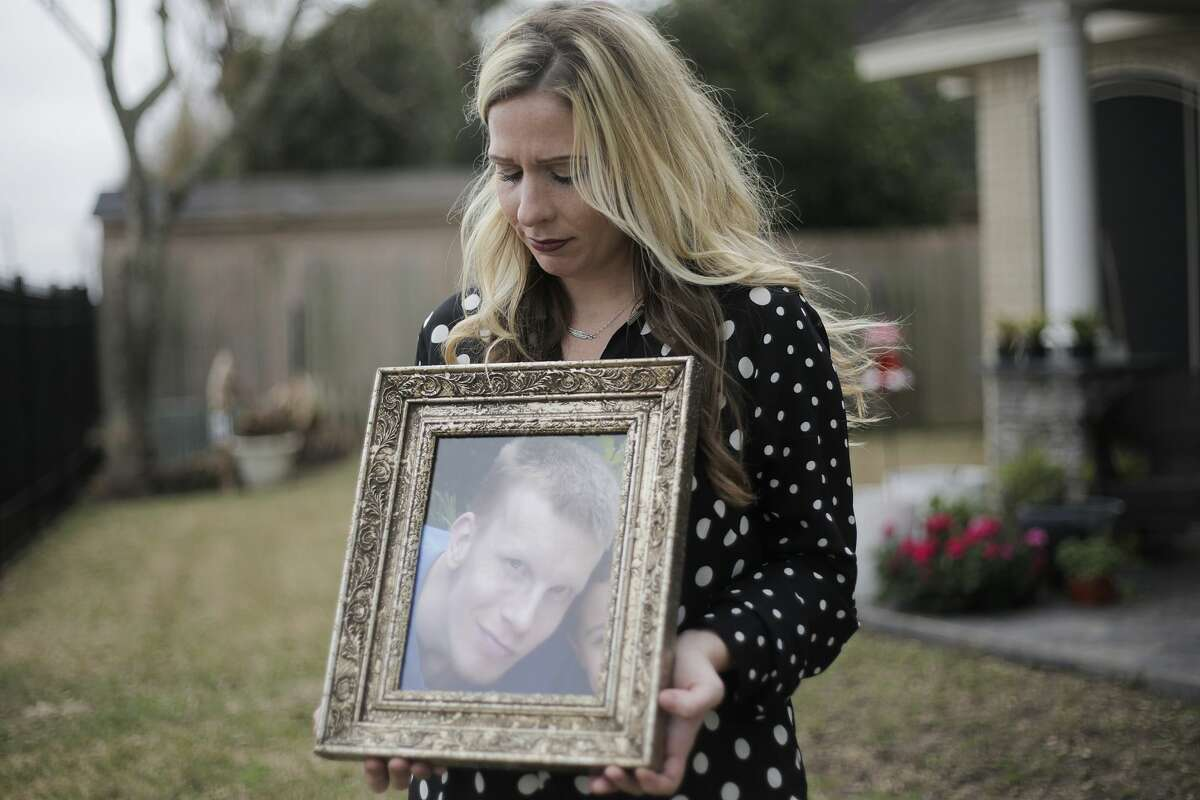 Regina Tran holds a photo of her brother, Travis Hogan, whodied in 2016 after being removed from the hearttransplant waiting list at Baylor St. Luke's Medical Center.