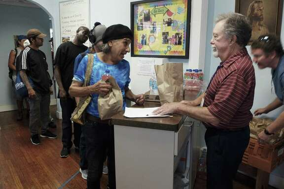 Volunteer Gates Whiteley, right, distributes sack lunches to the homeless at Christian Assistance Ministries in downtown San Antonio on May 3, 2018. The annual count of homeless people in Bexar County in January showed a steep rise in those living on the street. CAM serves 75 sack lunches to the needy each day.