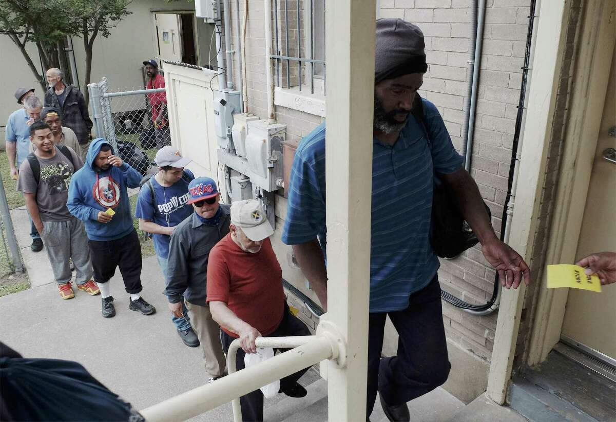 Some men get in line to receive tickets for a free sack lunch at Christian Assistance Ministries in downtown San Antonio on May 3, 2018.