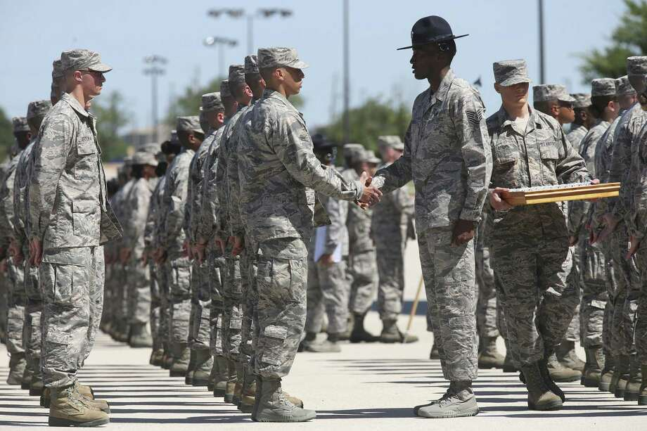 A training officer presents trainees with a coin during an Airman's Coin Ceremony at Join Base San Antonio-Lackland, Thursday, May 25, 2017. A total of 645 graduate the seven and a half week basic training. Photo: JERRY LARA /San Antonio Express-News / © 2017 San Antonio Express-News