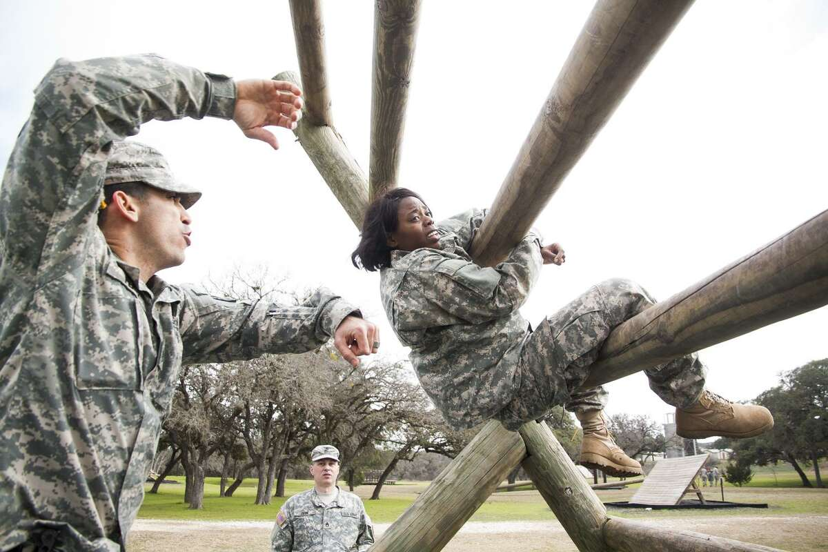 Ssg. Kelli Anderson listens to instructions from her sponsor Ssg. Gilberto Perez while she tries to complete the Reverse Climb obstacle Friday Feb. 6, 2014 during the 80th Training Command's Best Warrior Competition at Camp Bullis.