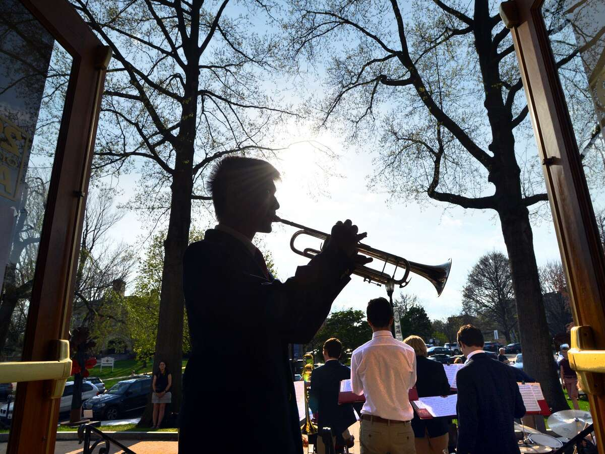 Greenwich High School freshman Artemis Shung, 14, warms up on his trumpet before playing with the GHS Jazz Band during the opening night of Art to the Avenue, the Greenwich Arts Council's spring art celebration on Greenwich Avenue Thursday.
