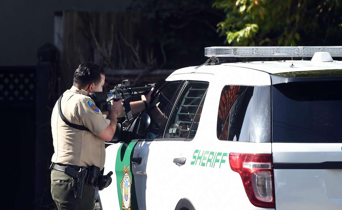 A police officer takes aim at an apartment complex during an active shooter situation in Mill Valley on Thursday, May 03, 2018.