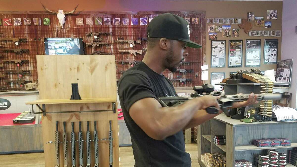 NRATV host Colion Noir checks out an AR-15 at a Dallas, Texas gun shop. (Molly Hennessy-Fiske/Los Angeles Times/TNS)