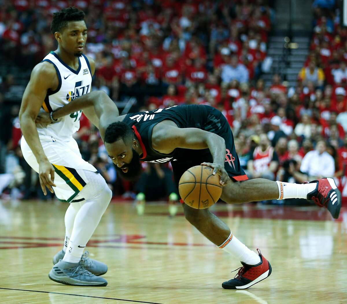 Houston Rockets guard James Harden (13) is tripped up as he dribbles past Utah Jazz guard Donovan Mitchell (45) during the second half in Game 2 of an NBA basketball second-round playoff series at Toyota Center on Wednesday, May 2, 2018, in Houston. ( Brett Coomer / Houston Chronicle )